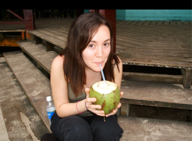 Laura sipping a coconut in Costa Rica after graduation from Yale.
